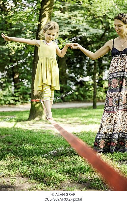 Young girl with mother walking slackline in park