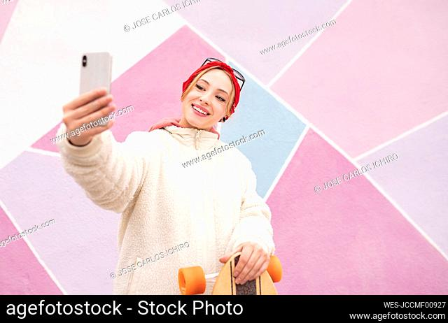 Young woman with skateboard taking selfie while standing against multi colored wall