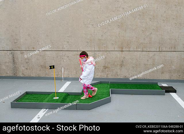 girl in pink doctor costume and face mask playing mini golf
