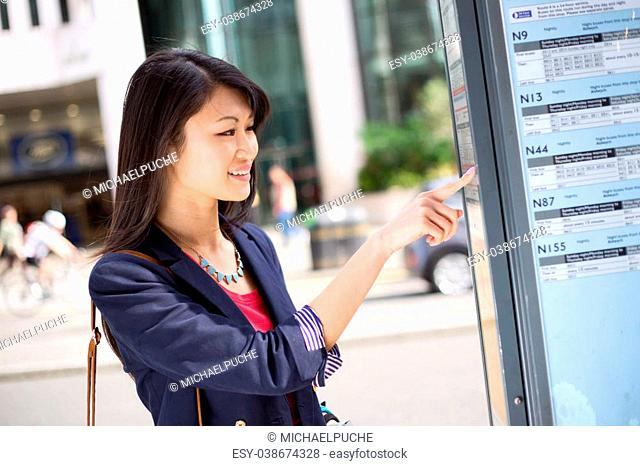young chinese tourist checking the bus time table