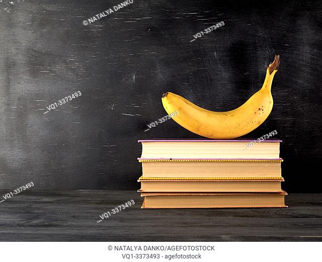 closed books with yellow sheets and ripe banana on a black chalk board background, copy space, back to school concept