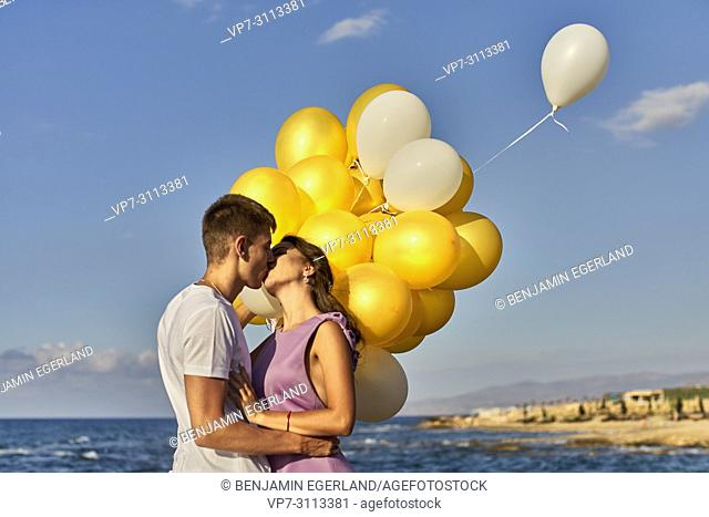 couple kissing, balloons, seaside