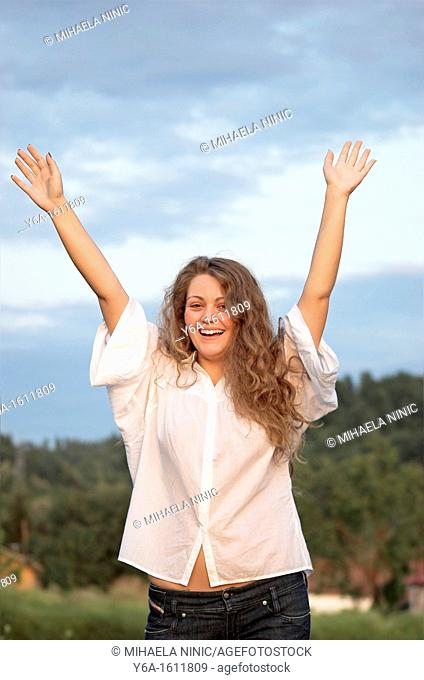 Portrait of a smiling young woman outdoors with arms raised