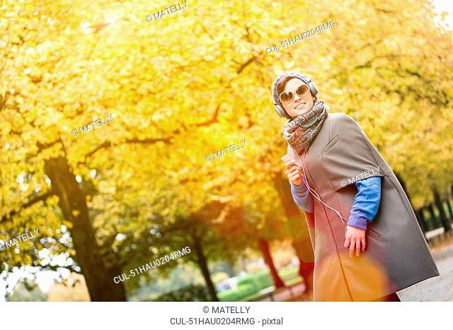 Woman listening to headphones in park