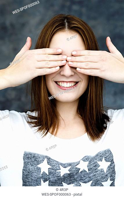 Young woman covering eyes, smiling