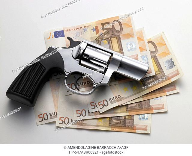Euro banknote and revolver on white background