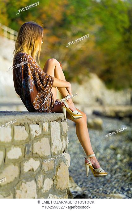 Young woman sitting on wall atop beach watching sunset