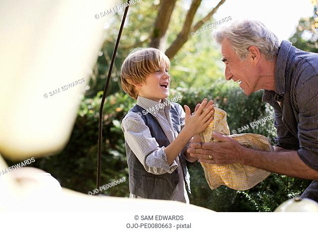 Grandfather and grandson wiping hands with cloth in front of car in driveway