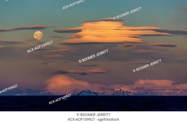 Dramatic Lenticular clouds share an evening sky with a full moon overlooking the Gerlache Strait, Antarctic Peninsula