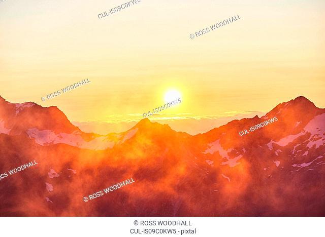 Sun glowing on horizon over mountain range, Saas-Fee, Valais, Switzerland