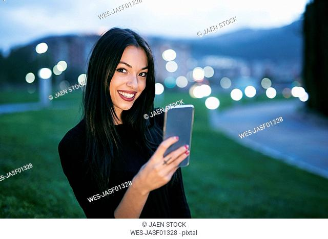 Portrait of smiling young woman with smartphone at twilight