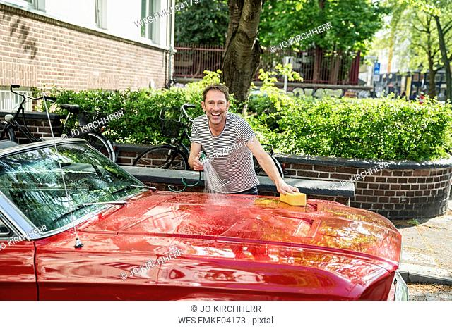Smiling mature man washing his sports car