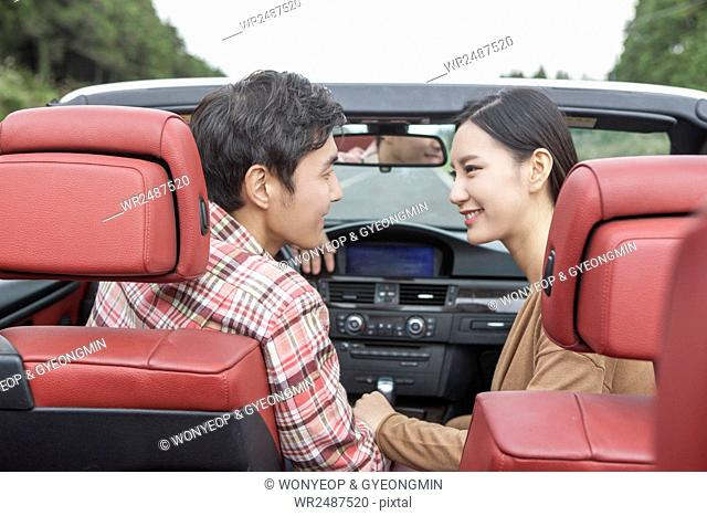 Side view portrait of young smiling couple in a car holding hands face to face