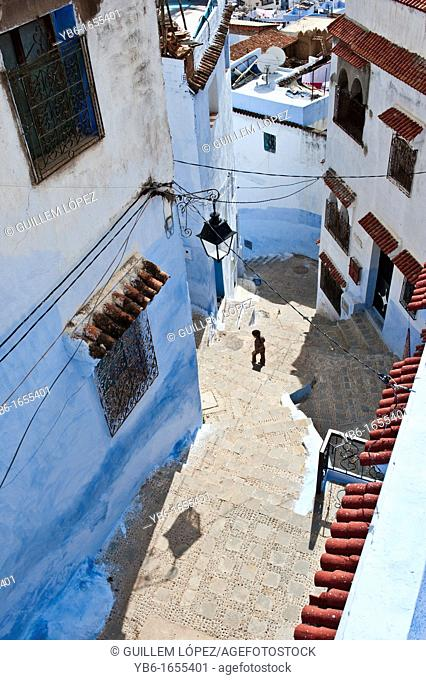 High view of a kid walking in the blue walled old medina of Chefchaouen, Morocco