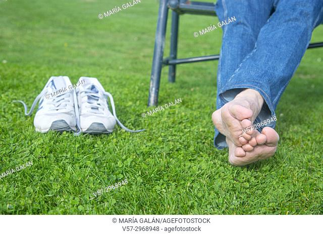 Sitting man's feet on the grass