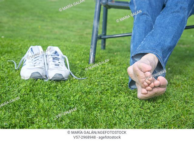 Sitting man's feet on the grass