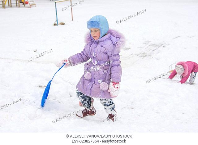 Five-year girl riding on a snowy icy hill