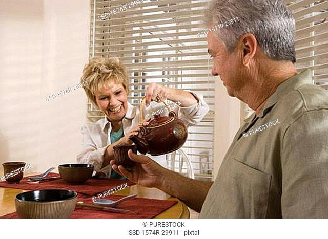 Mature couple by breakfast table pouring tea into a cup