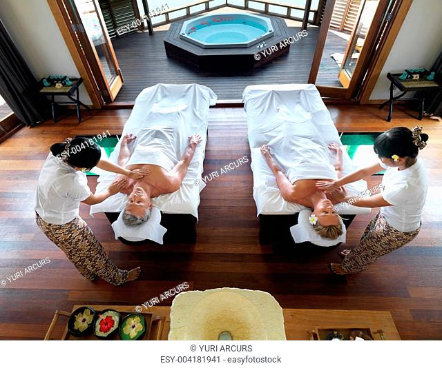Image of relaxed couple getting a massage at spa resort