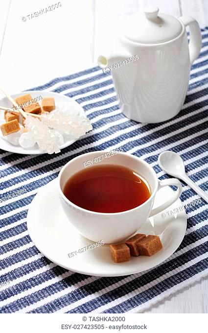 Cup with tea and teapot on blue striped background