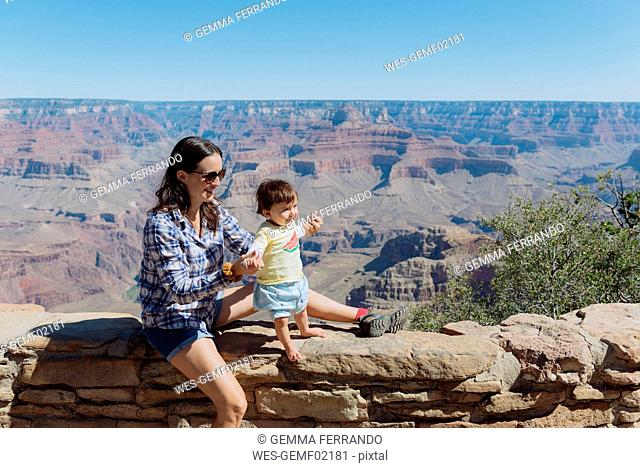 USA, Arizona, Grand Canyon National Park, Grand Canyon Village, mother and little daughter on a wall