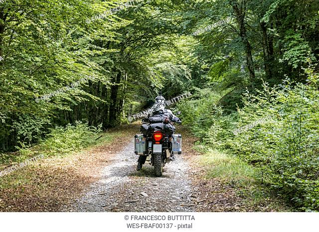 Father and son on a motorbike trip on a forest track
