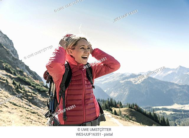 Austria, Tyrol, happy woman on a hiking trip in the mountains enjoying the view