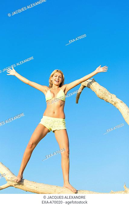 woman balancing on a tree trunk
