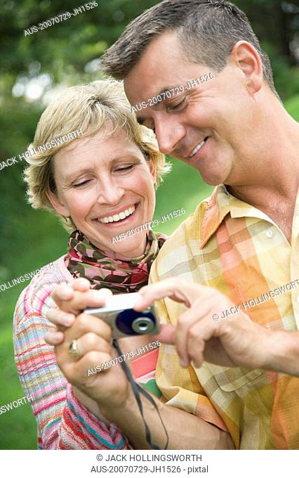 Close-up of a mature couple looking at a digital camera and smiling