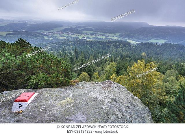 Polish-Czech border next to Bledne Skaly trail in Stolowe Mountains range, part of Sudetes, Poland. Machow town in Czech Republic on background