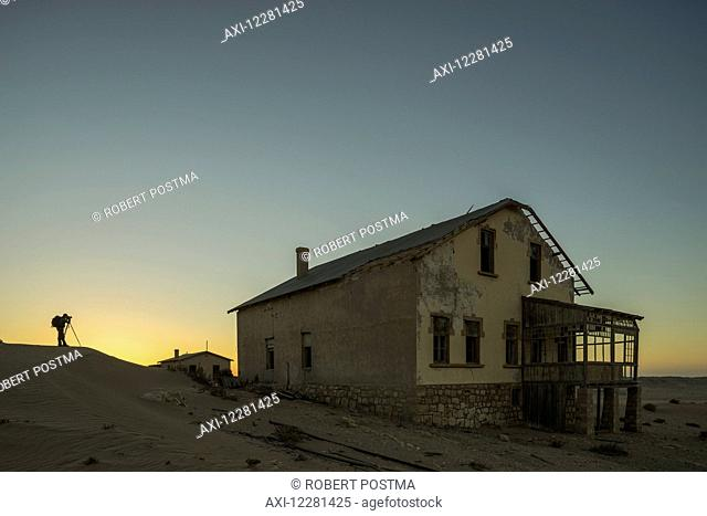 A person takes photos of the abandoned homes in the Namib desert at sunset; Kolmanskop, Namibia
