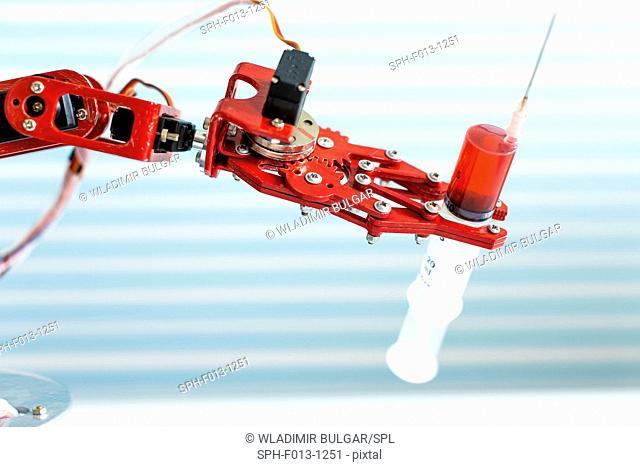 Robotic arm holding medical syringe