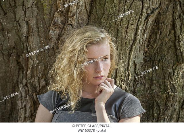 Blonde teenage girl sitting in front of a tree