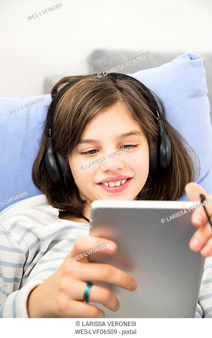 Portrait of smiling girl using tablet and headphones at home