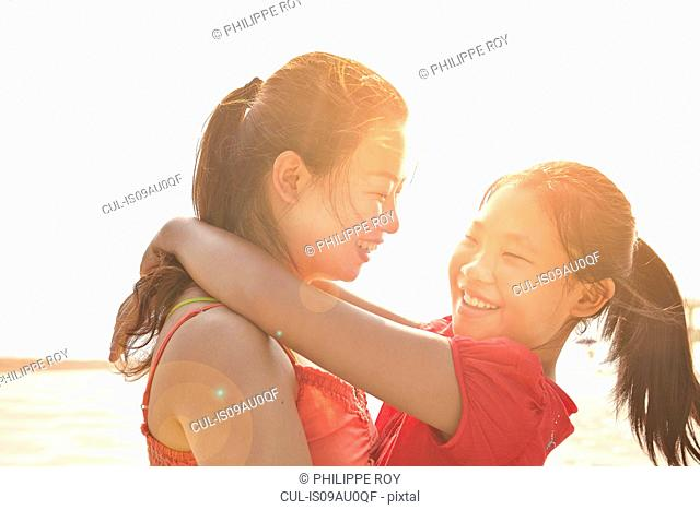 Mid adult woman and daughter hugging on beach, Zhuhai, Guangdong, China