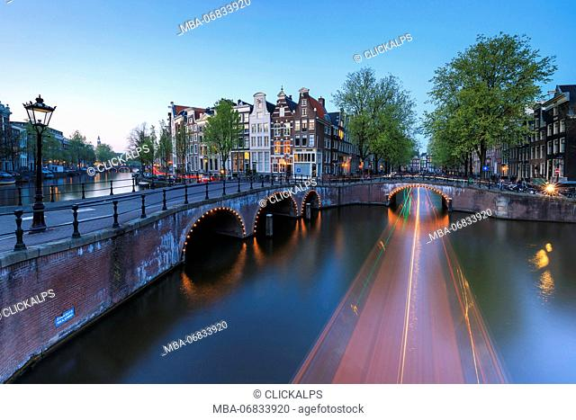 Dusk lights on the typical buildings and bridges reflected in a typical canal Amsterdam Holland The Netherlands Europe