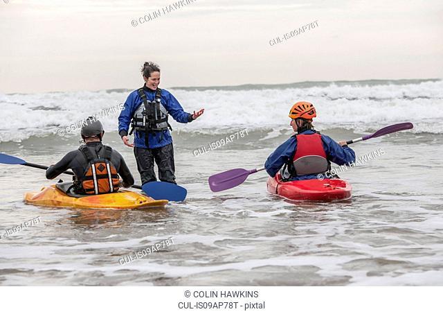 Female instructor talking to people in sea kayaks