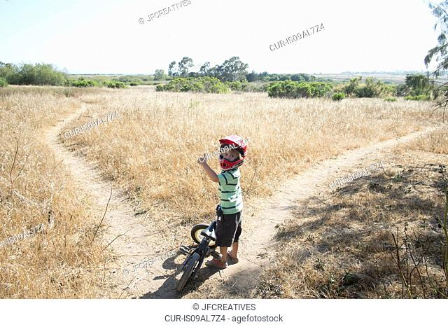 Young boy on path in field with bike