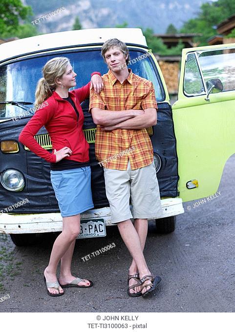 Young couple standing in front of van
