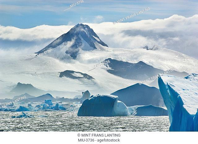 Icebergs and mountains on coastline, Neumayer Strait, Antarctica