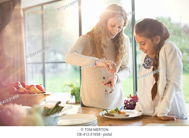 Pregnant mother serving food for daughter at dining table