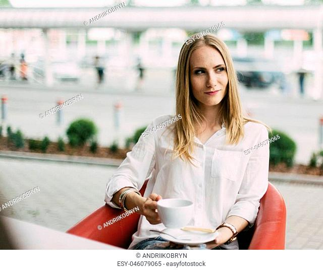 Portrait of charming smiling businesswomen posing while resting during coffee break, while sitting in modern cafe interior