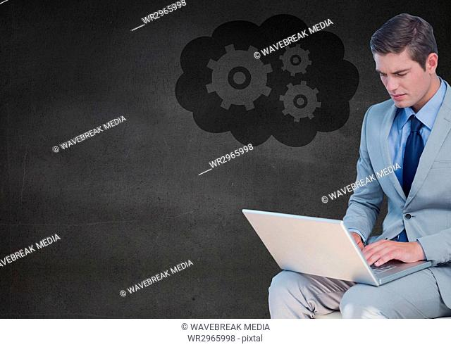 Business man with laptop against grey wall and cloud with gear graphic