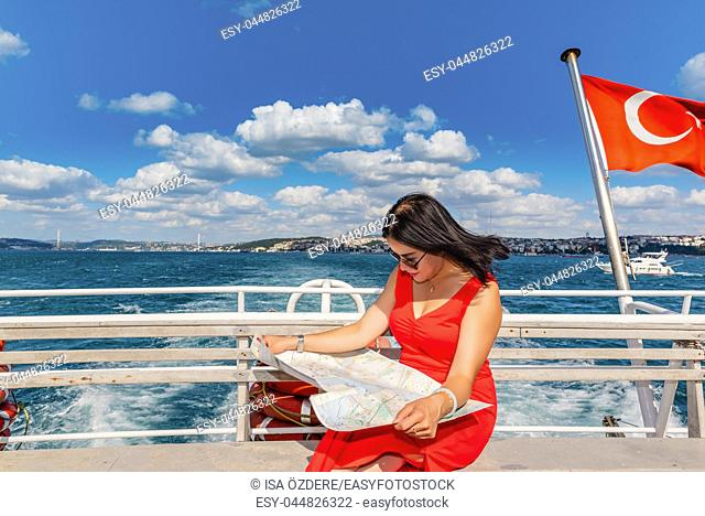 Beautiful Chinese woman looks at Istanbul map while cruising in Istanbul,Turkey