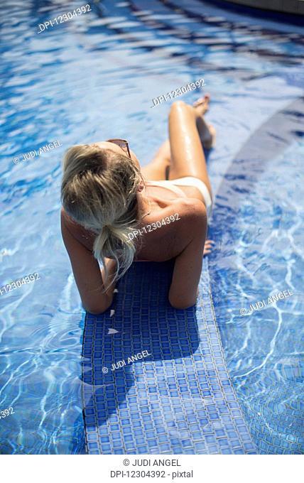 Woman at a resort enjoying the pool; Island of Hawaii, Hawaii, United States of America