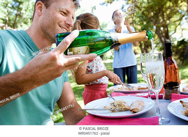 Side profile of a mid adult man with their two children in a park and pouring champagne