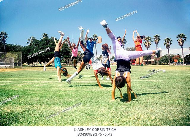 Schoolgirl soccer team doing cartwheel celebration on school sports field