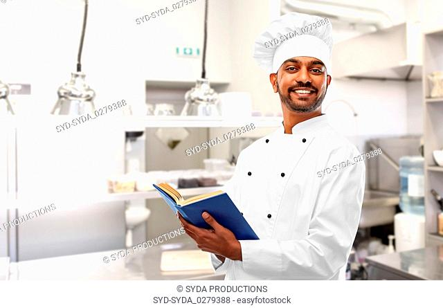 happy indian chef with cookbook at kitchen
