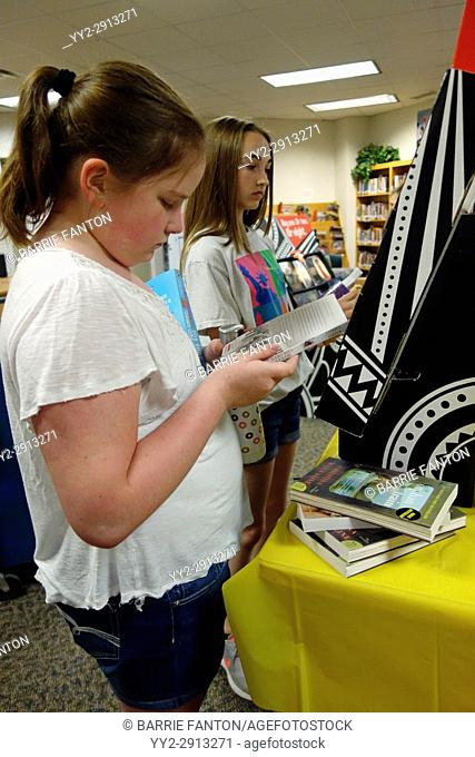 6th Grade Girls Looking at Books in Library, Wellsville, New York, USA