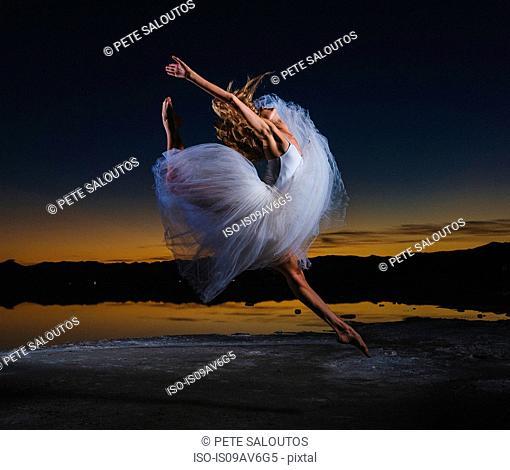 Young female ballet dancer leaping over Bonneville Salt Flats at dusk, Utah, USA